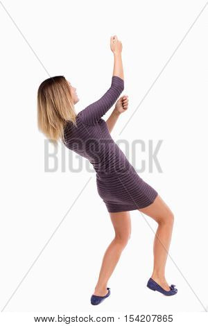 back view of standing girl pulling a rope from the top or cling to something. girl  watching. backside view of person.  Isolated over white background. Girl in dress from the top rope pulls
