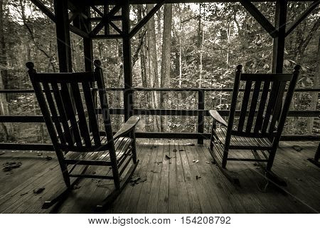 Two wooden rocking chairs on an old front porch. Shot in black and white with horizontal orientation.