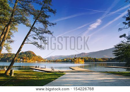Amazing View On Bled Lake. Autumn in Slovenia Europe. View on Island with Catholic Church with Sky and Mountains in Background.
