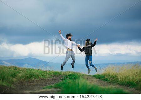 Couple Bouncing On Gray Sky