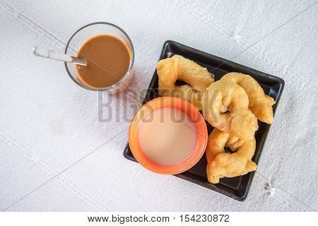 deep-fried doughstick and sweetened condensed milk with coffee