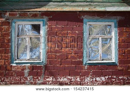 Two old obsolete windows in faded painted wooden frame in red brick wall