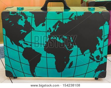 Big Green Suitcase with Globe Cartography Print on it Travel Concept