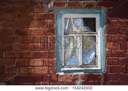 Red peeled off brick wall with old obsolete window in faded painted wooden frame closed by reflecting material protecting from sunlight and heat