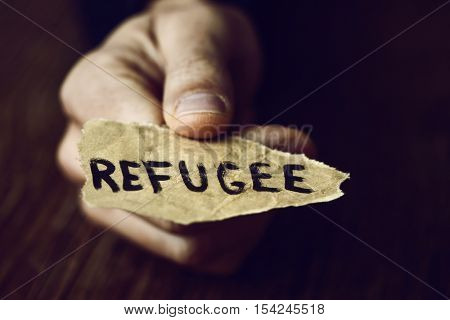 closeup of the hand of a young man with a piece of paper with the word refugee, with a dramatic effect