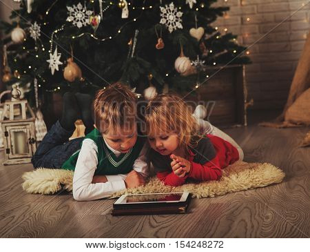 modern technology concept- kids selecting Christmas presents on touch pad