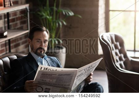 Being informed. Pleasant good looking attractive man holding a newspaper and reading the latest news while being in the office