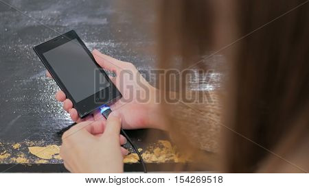 Woman's hand plugging black lightning charging cable into smartphone - USB data cable connecting on modern gadget