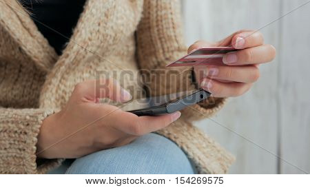 Young woman buying goods from the internet and entering number security code from credit card on smartphone. Online, technology and internet concept. White wooden background