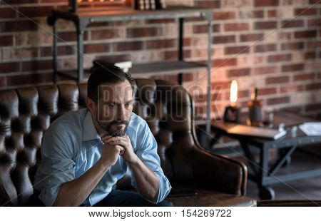 Serious look. Attractive thoughtful stylish man holding his chin and looking thoughtfully while sitting on the couch