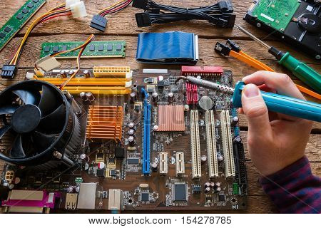 man soldering computer hardware repair close up