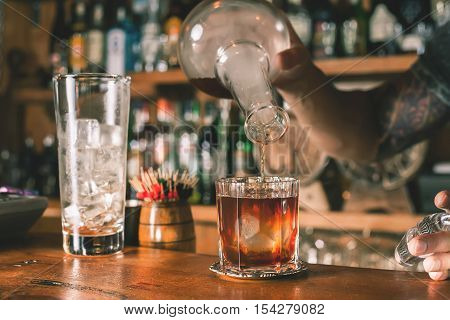 Closeup barman is making cocktail at night club