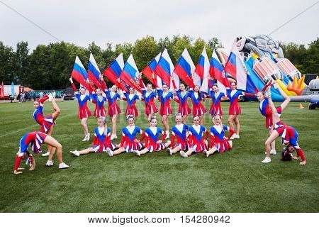MOSCOW, RUSSIA - AUG 20, 2016: Team of girls cheerleaders poses at playground during the Moscow City Championship of combat deployment in Luzhniki.