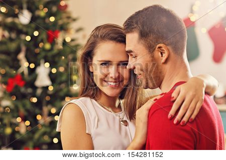 Picture showing young couple hugging over Christmas tree