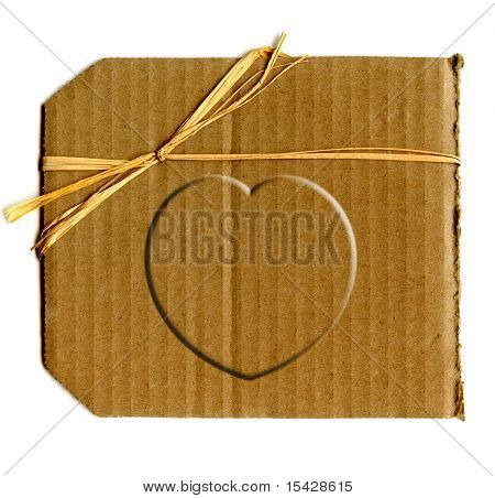 Cardboard Heart On Piece Of Corrugated Cardboard With Twine Bow