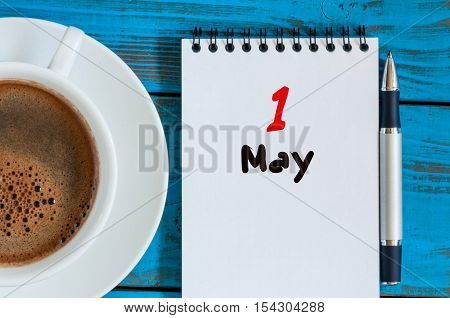 May 1st. Day 1 of month, calendar on white notepad with morning coffee cup at work place background. Spring time, Top view.