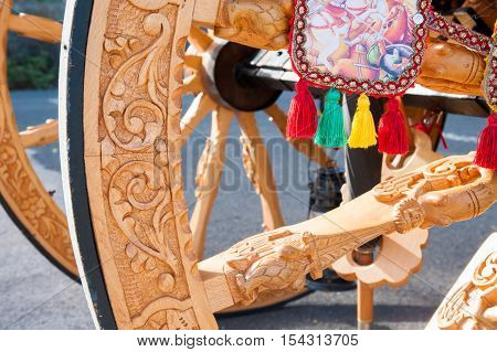 Closeup view of a wooden carved wheel of a typical sicilian cart during a folkloristic show