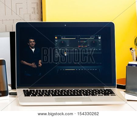 PARIS FRANCE - OCT 28 2016: Apple Computers website on new MacBook Pro Retina with OLED Touch bar in geek creative room showcasing Apple Keynote presentation of DJ capabilities of the new OLED bar