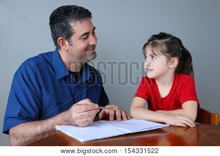 Father (man age 35-45) helping his daughter (girl age 6 -7) with her school project at home. Family lifestyle and education concept