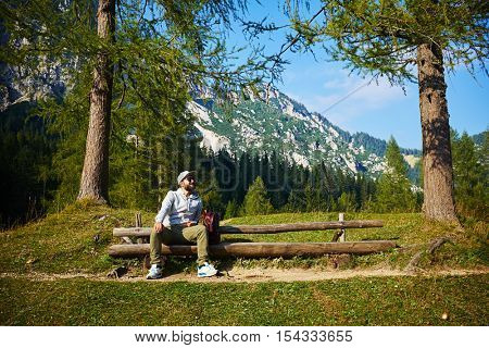 Wide shot of bearded man who is looking at the sky while sitting on the bench. Enjoying stunning vista of mountains on a cloudless gorgeous day