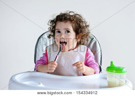 Little toddler child (girl age 2-3) waits for meal time. Childhood and children health care concept. Real people copy space
