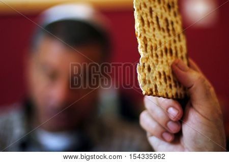 A man is blessing on Matzah (unleavened bread) while another wearing a kippah (scullcap) reads the Haggadah (traditional text) during blessings for the Jewish holiday of Passover Dinner