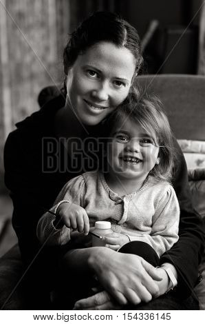 Young mother hold her baby on her laps smiles to to the camera(BW).