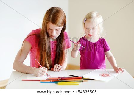 Toddler Girl And Her Mom Drawing With Pencils