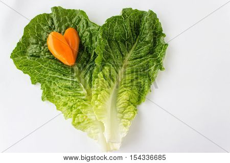 horizontal image of two pieces of green romaine lettuce placed together in a heart shape with a little orange pepper shaped in a heart placed on top of lettuce isolated on white with room for text.