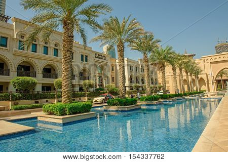 DUBAI, UAE - OCTOBER 11, 2016: The entrance to the Palace Hotel in Dubai surrounded by Palm Trees and neighbouring the mighty Burj Khalifa