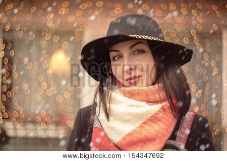 woman with ironic smile on blurred lights background with snow
