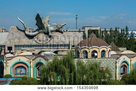 Roof of building decorated by the dragon body. Building in the asia theme park.