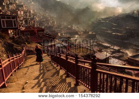 Buddhist nun walking down stairway at Larung gar in a warm and foggy morning time Sichuan