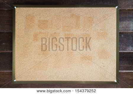 Blank cork board on wooden wall, stock photo