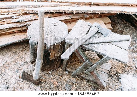 Firewood chopping workplace with axes close-up. Left outside tools in winter. Cold, early frosts, hoar concept