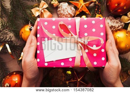 Hands put gift under Christmas tree, blank card. Man holding pink box with present near festive decorations, free space for signature or greeting