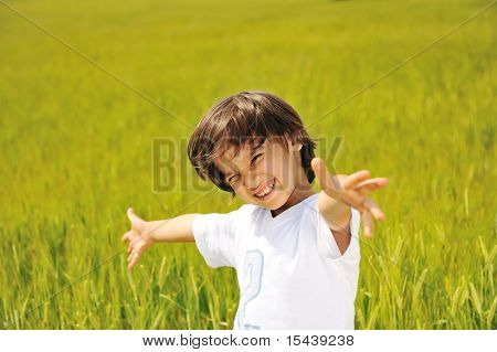 Happy kid on green field with widely opened arms