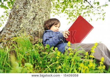 Happy child reading the book under the tree