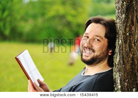 Young man reading book in nature