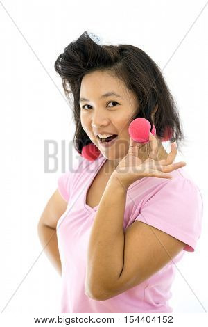 pretty young adult woman with hair curlers on white background (selective focus at hair curler)