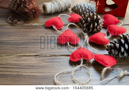 Christmas or New Year background. Making decoration for fir tree felt heart garland and bobbins on wooden rustic table. Winter holidays concept. Copy space.