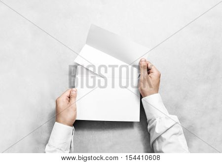 Hand holding white blank envelope and folded leaflet mockup, isolated. Arm hold empty brochure template mock up. Greeting card flyer design. Invitation printing display. Reading writing in envelope.
