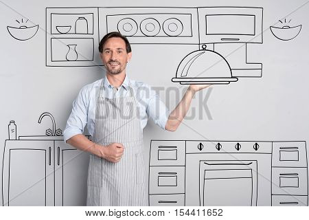 Serving the dinner. Elated positive good looking man holding the tray with the dish and smiling while standing in the kitchen