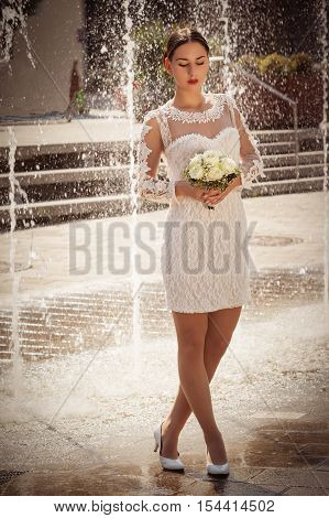 Slim bride in the short lace wedding dress and bridal bouquet before a fountain