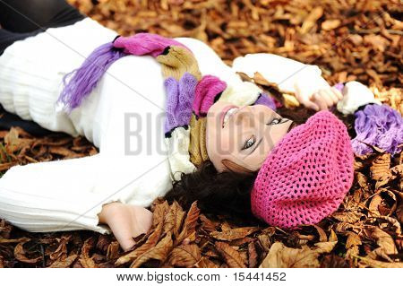 Close-up portrait of an beautiful autumn woman laying on fall leafs