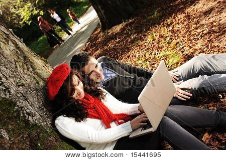 Young couple, male and female sitting in park and studying and working together with notebook , fall period