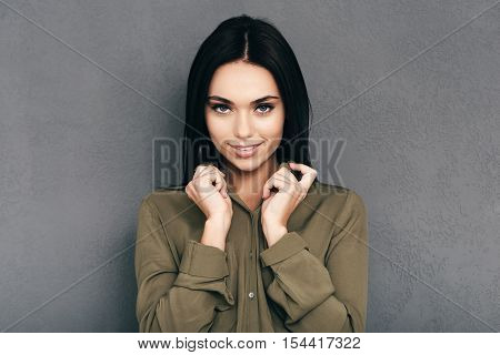 Stylish beauty. Attractive young woman touching her shirt collar and looking at camera with smile while standing against grey wall