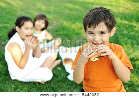 Small group of children in nature eating snacks together, sandwiches, bread