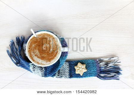 frothy cappuccino with cinnamon in a white cup wrapped in a blue scarf top view / for prolonging the warming effect