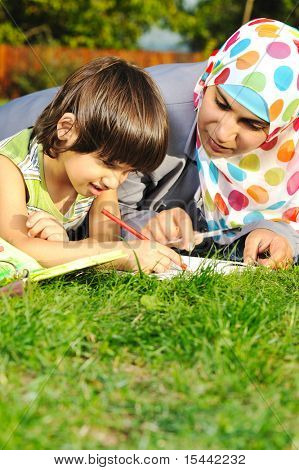 Mother with son, education in nature, laying on grass with notebook